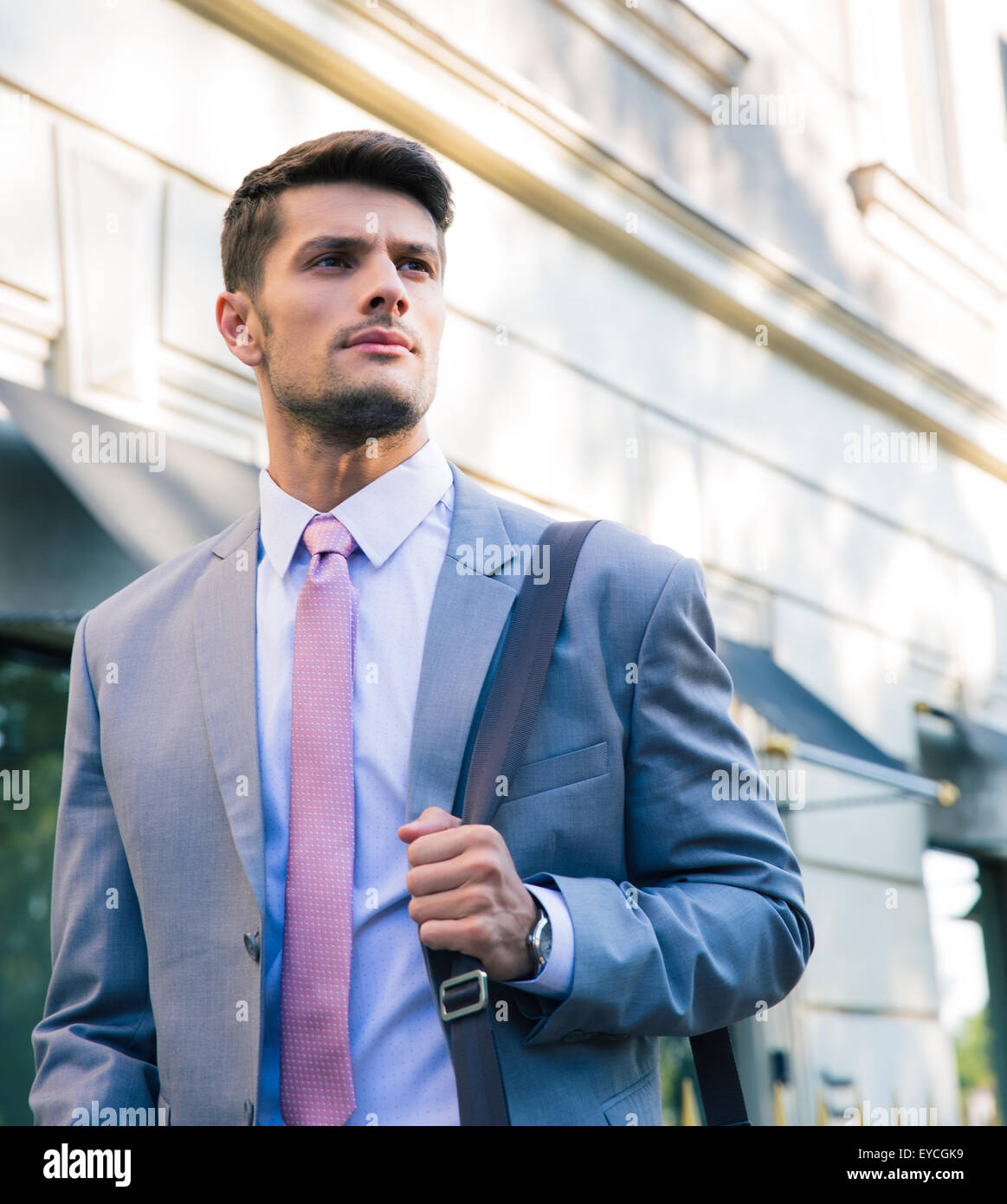 Portrait of a confident young businessman walking outdoors in town - Stock Image