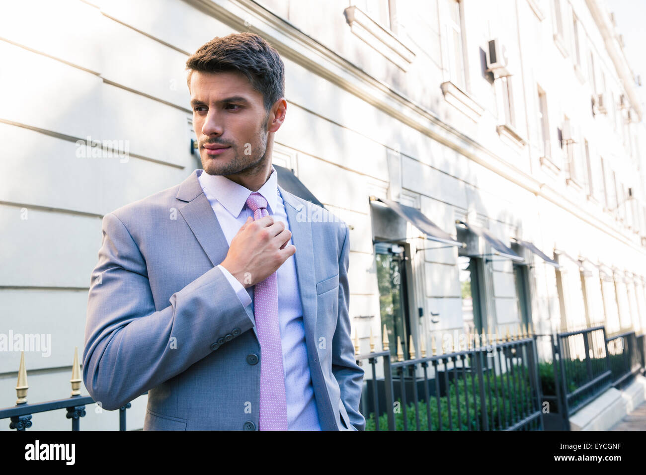 Confident businessman straightens his tie outdoors - Stock Image