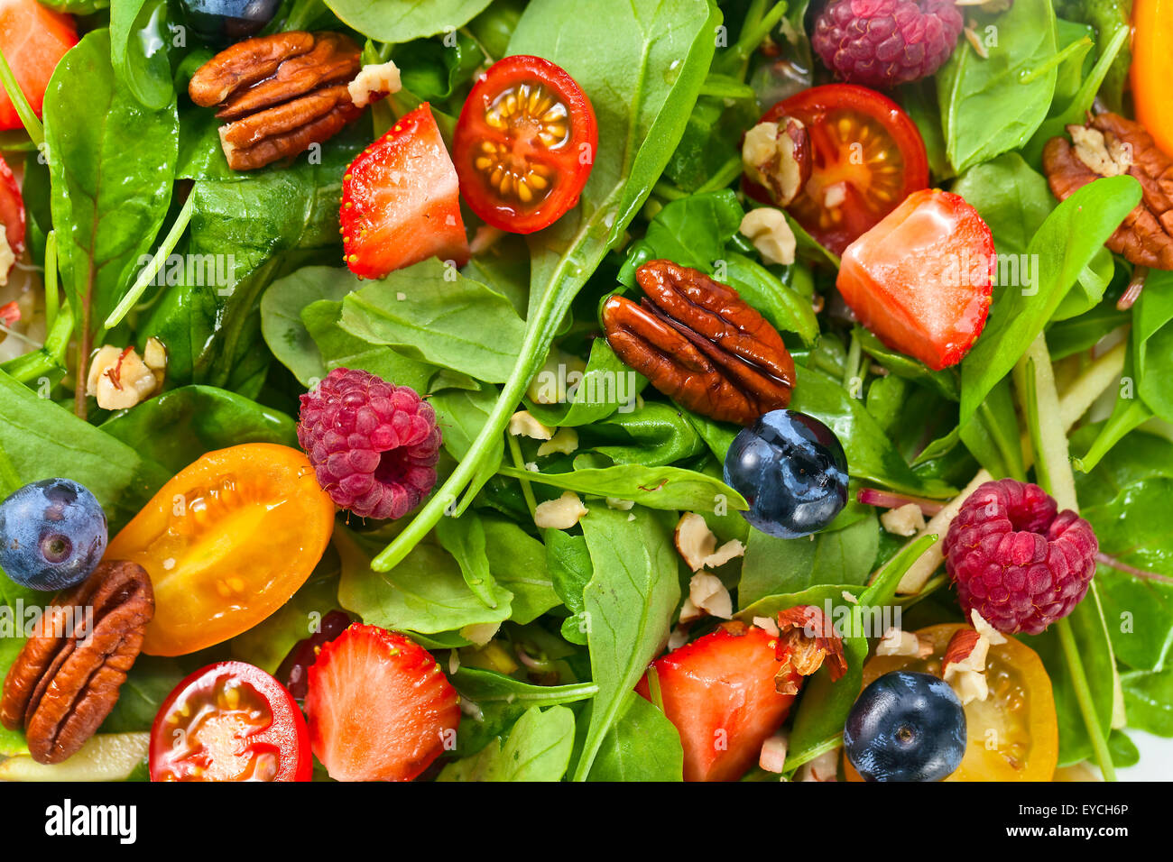 Green vegan salad with berries and nuts - Stock Image