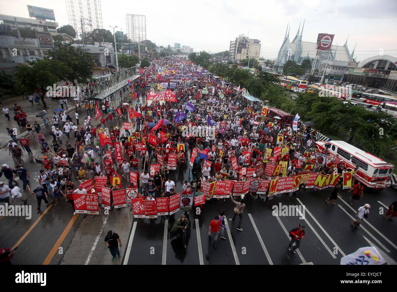Quezon City, Philippines. 27th July, 2015. Activists walk in the rain during a protest rally in Quezon City, the - Stock Image