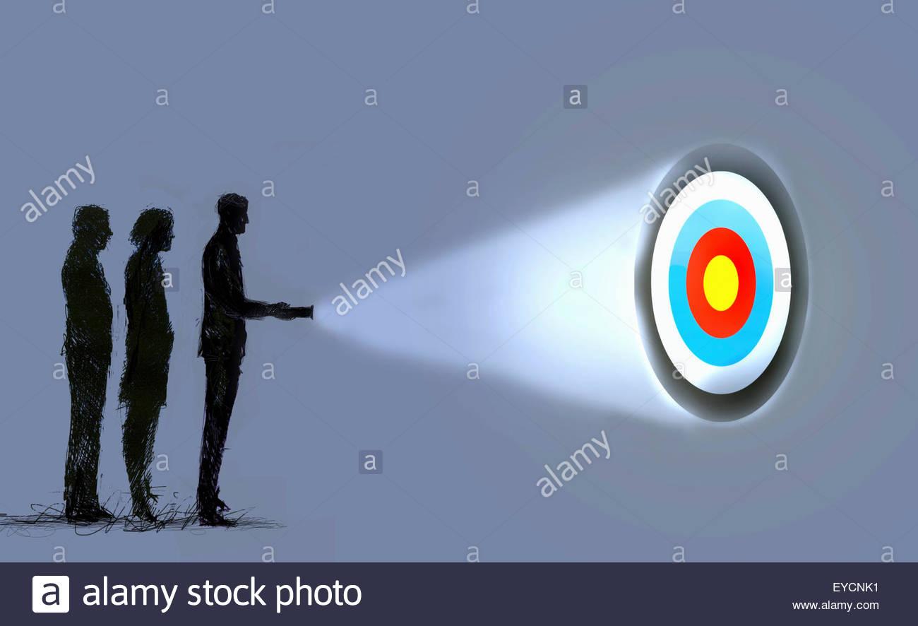 Business people shining light on target - Stock Image