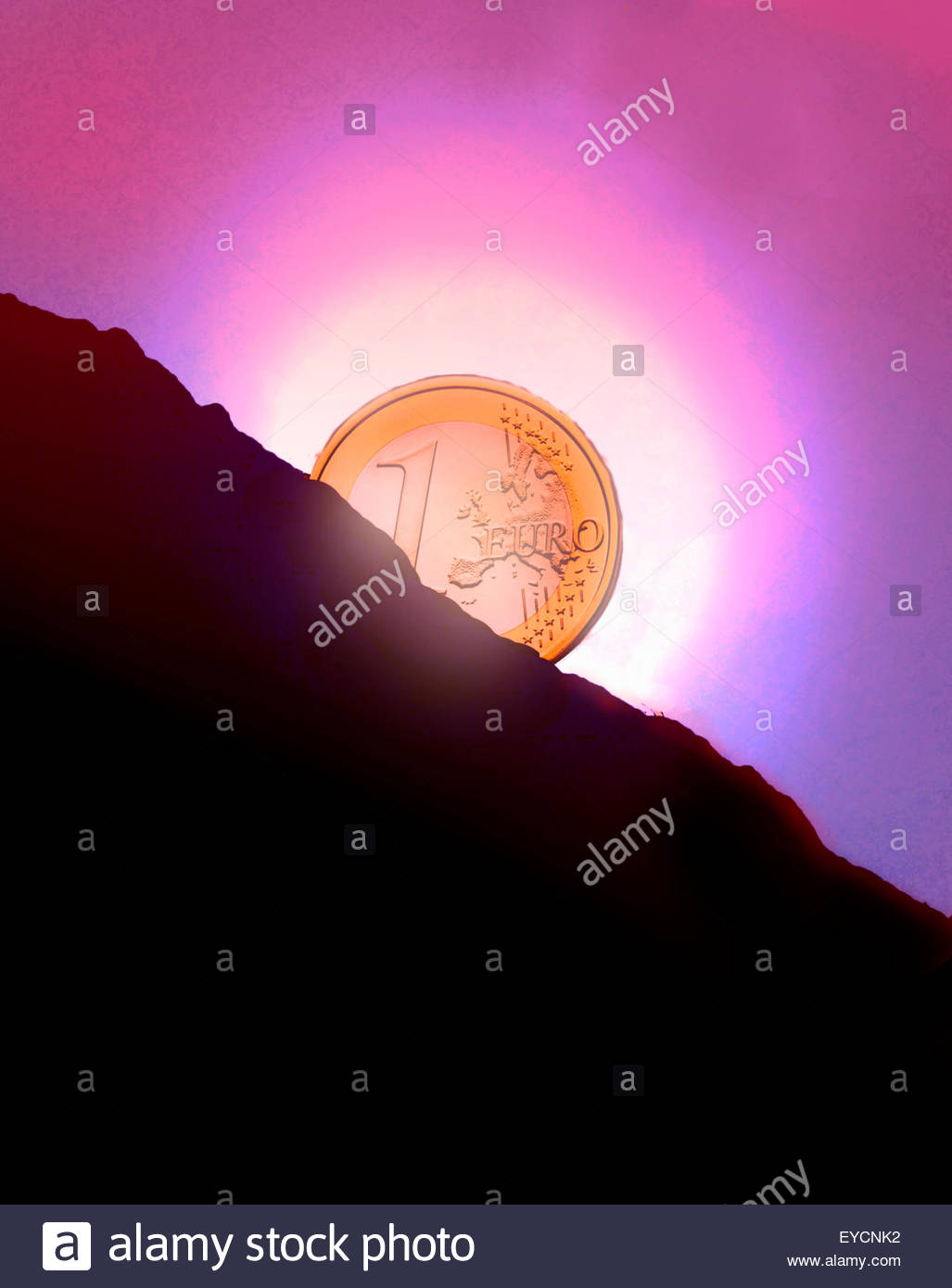 Glowing Euro coin sunset behind hillside - Stock Image