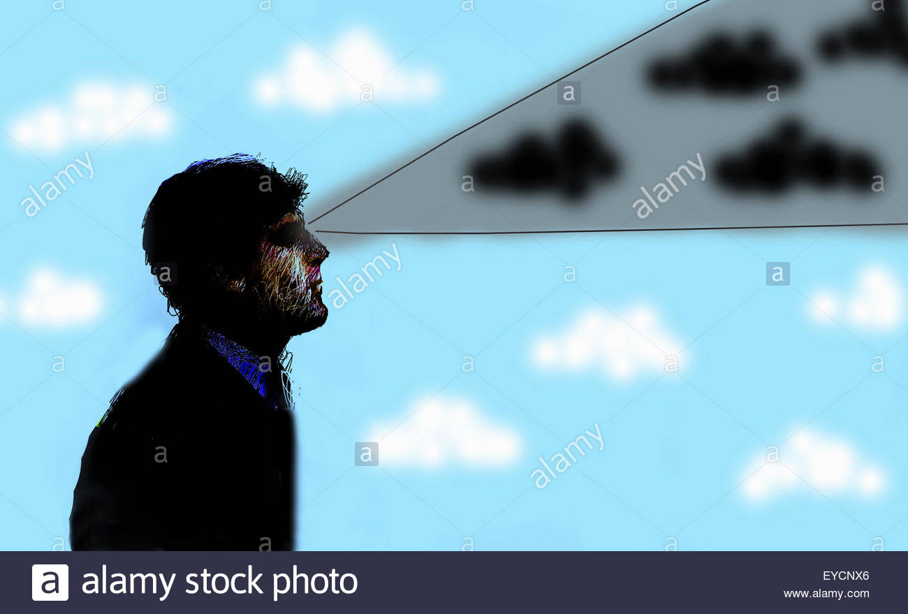 Businessman looking ahead with beam of gray cloudy sky - Stock Image