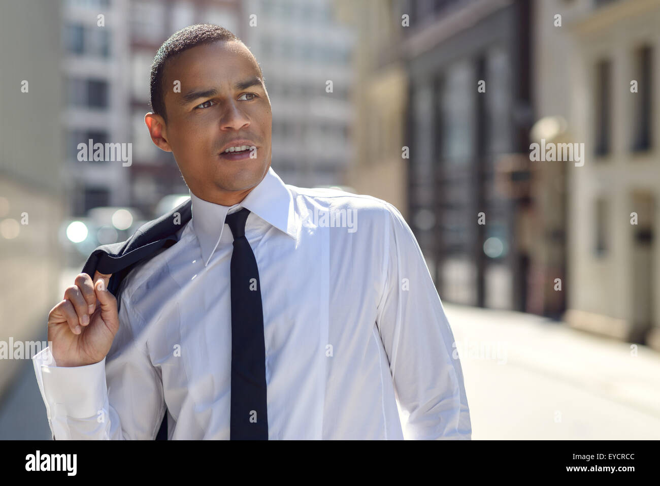 Handsome businessman walking in an urban street with his suit jacket slung over his shoulder as he looks up at the - Stock Image