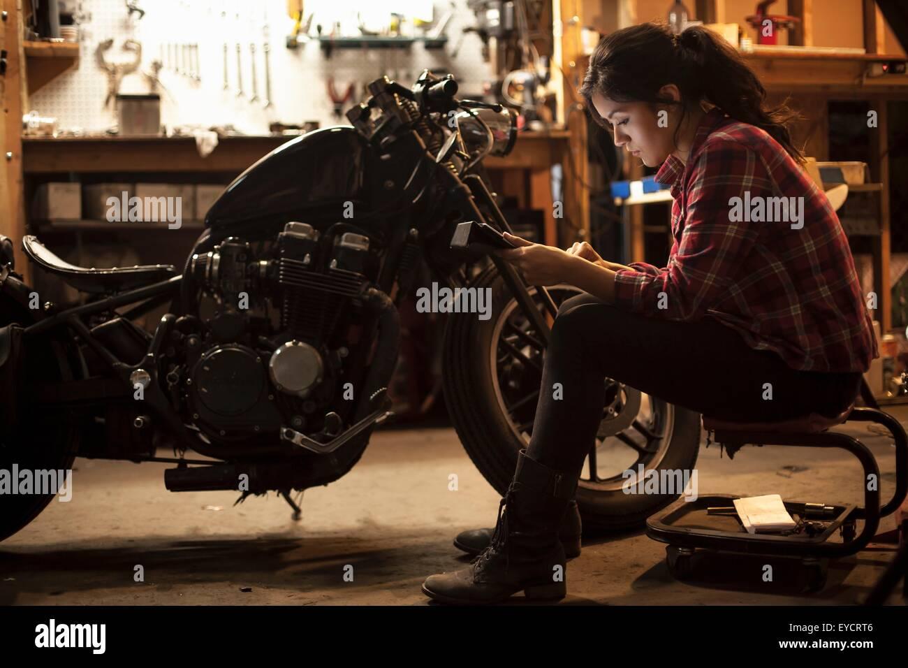 Female mechanic working on motorcycle in workshop - Stock Image
