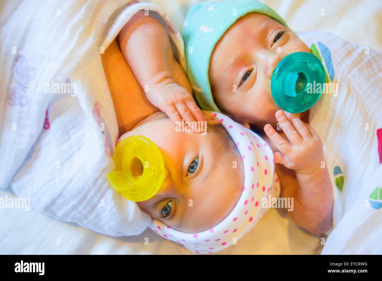 Twin baby sister and brother sucking on comforter - Stock Image