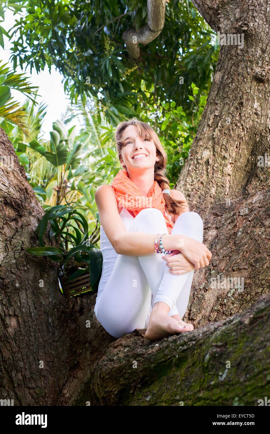 Portrait of young woman sitting in tree - Stock Image