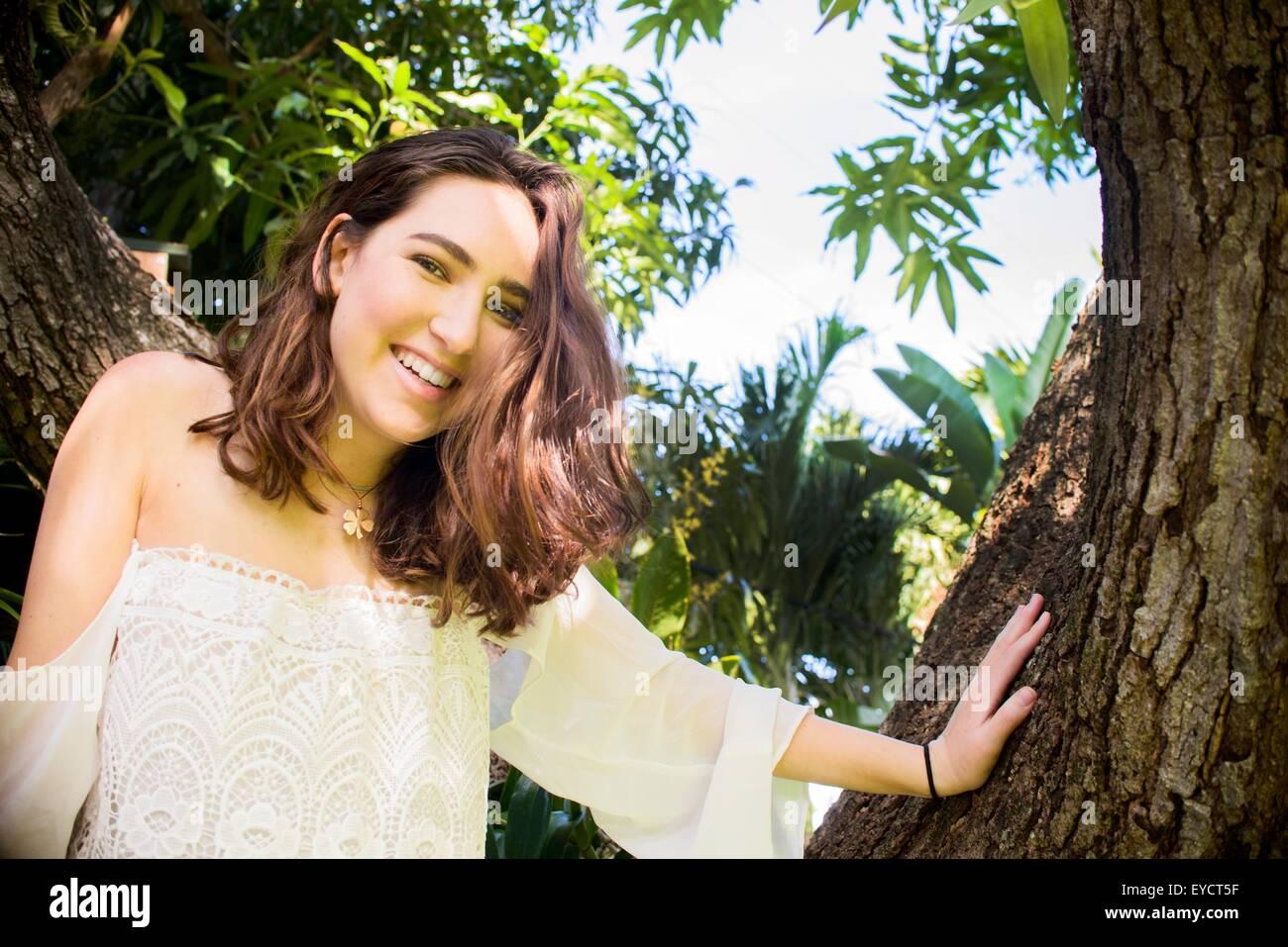 Portrait of teenage girl climbing tree - Stock Image