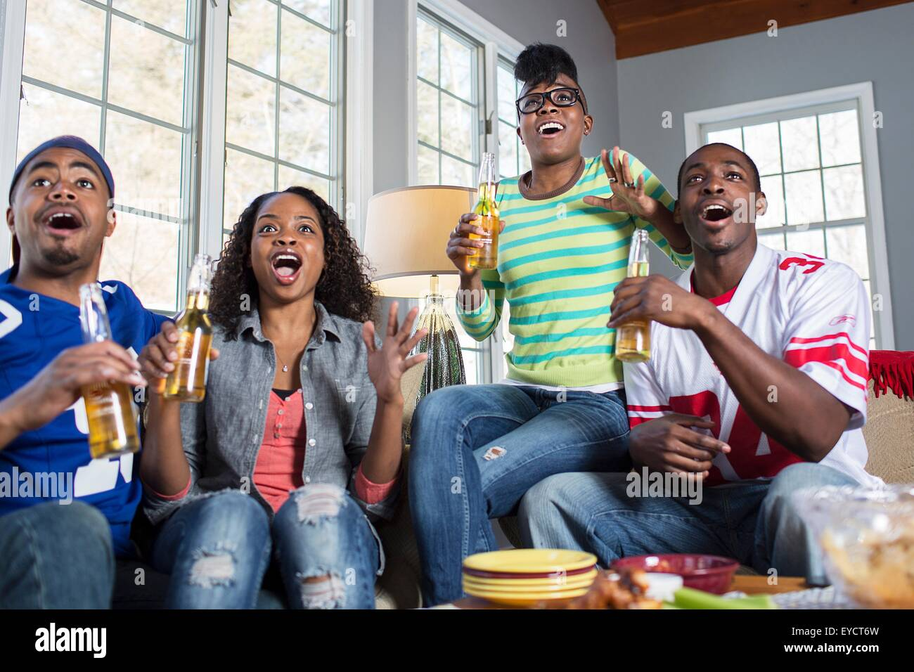 Four adult friends gasping open mouthed whilst watching TV from sofa - Stock Image
