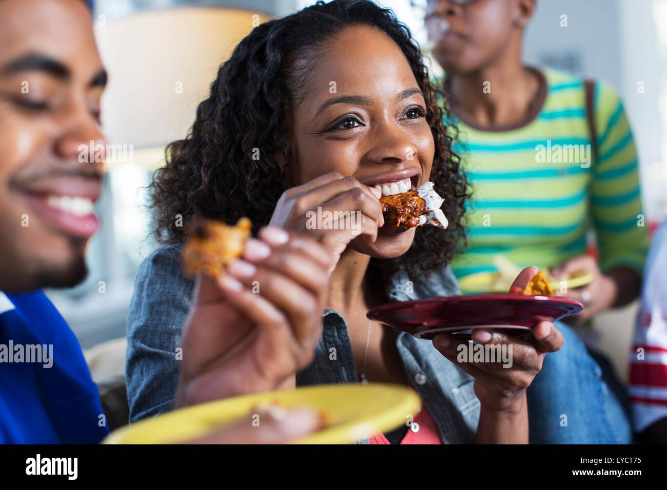 Three adult friends eating takeaway on living room sofa - Stock Image