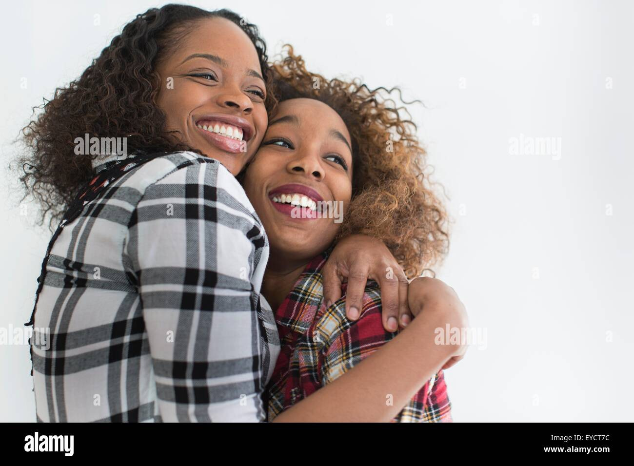 Studio portrait of two young women friends hugging - Stock Image