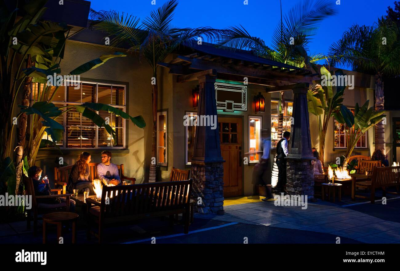 Customers dining out by restaurant open fire - Stock Image