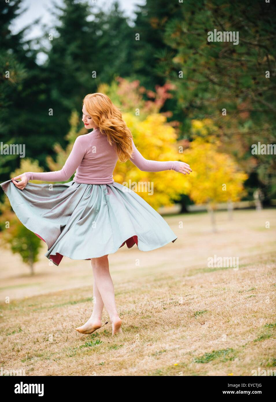 Young female dancer twirling and  lifting skirt in park - Stock Image