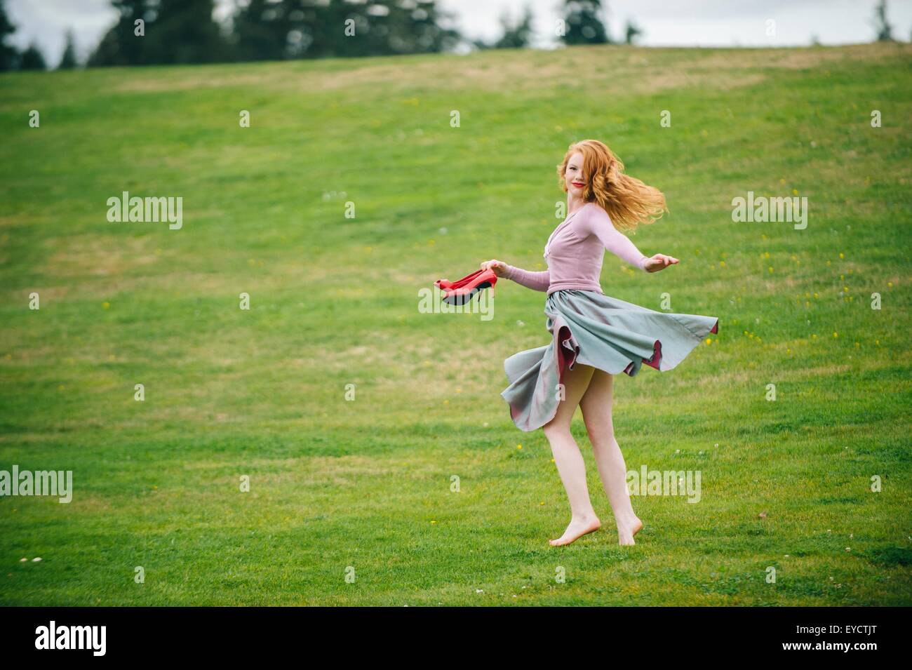 Portrait of young woman dancing in park holding red high heels - Stock Image