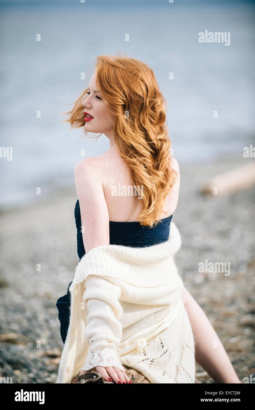 Young woman with long red hair looking over her shoulder on beach, Bainbridge Island, Washington State, USA - Stock Image