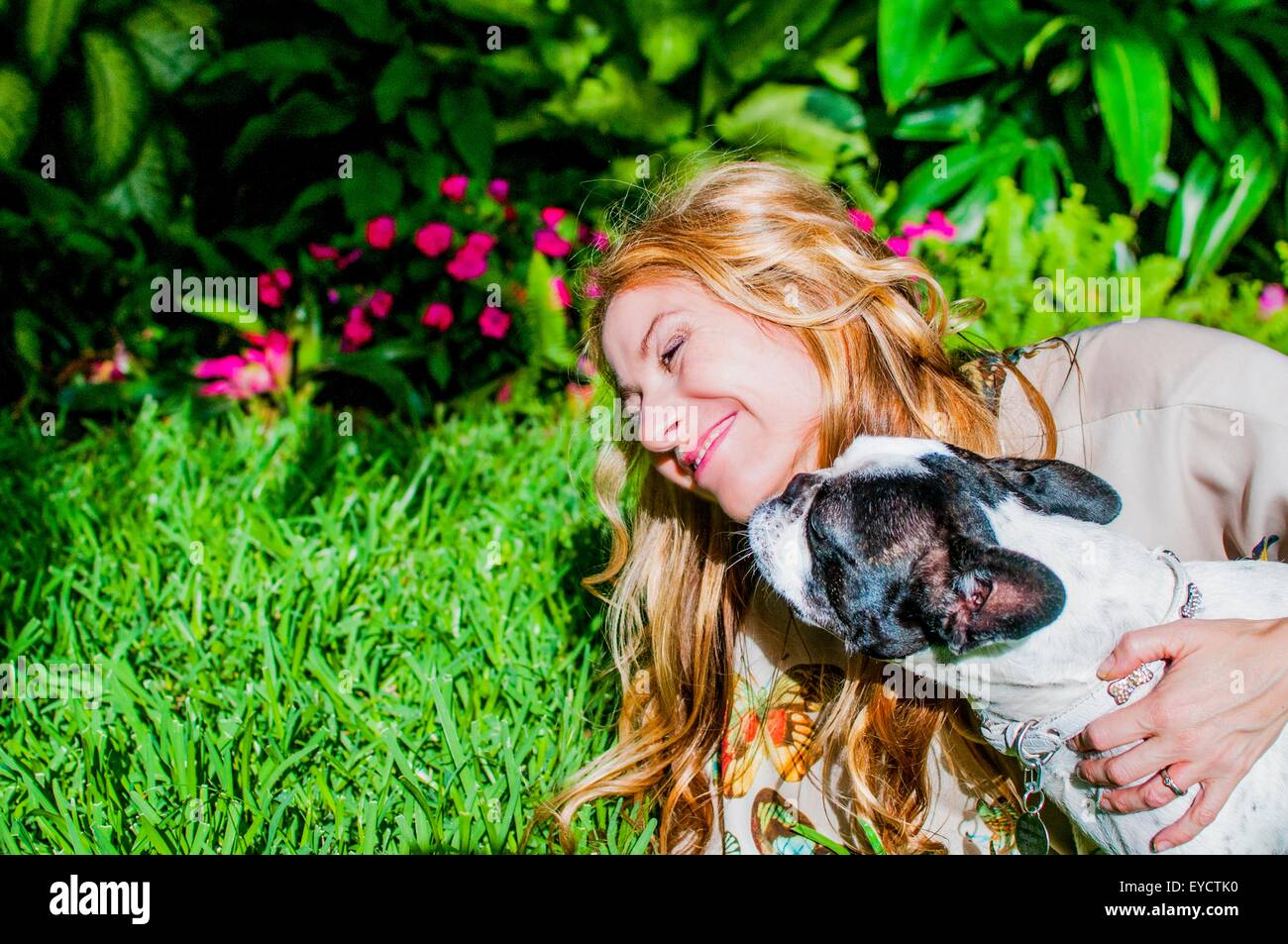 Dog licking woman's face in garden Stock Photo