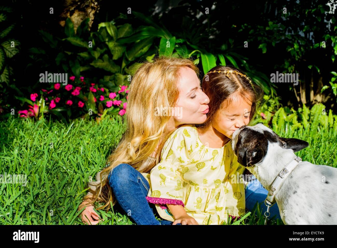 Dog licking girl's face in garden - Stock Image
