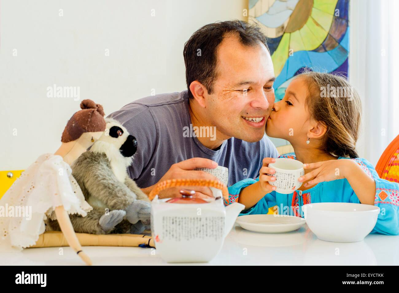 Girl kissing father on cheek at table - Stock Image