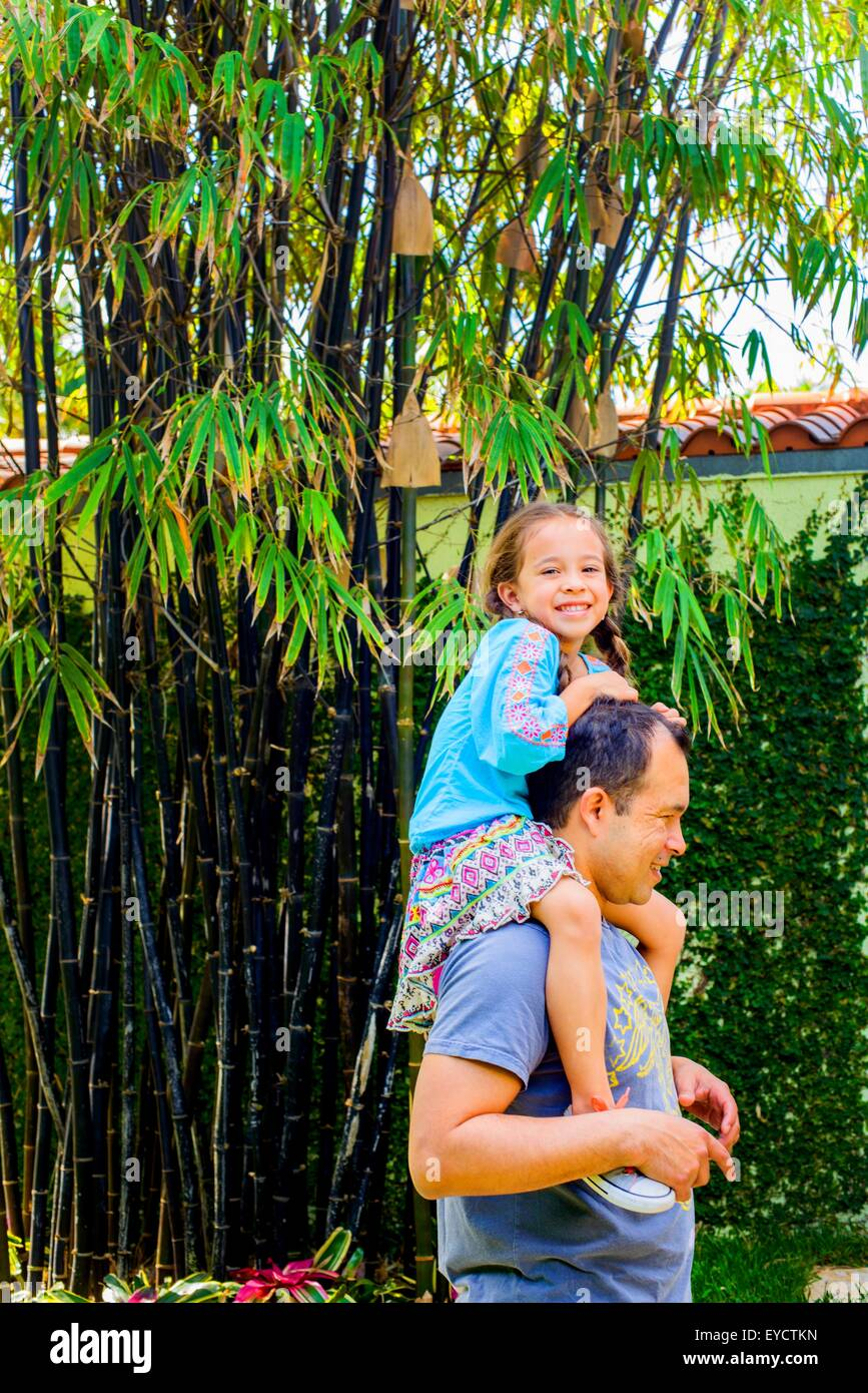 Portrait of girl getting a shoulder carry from father in garden - Stock Image