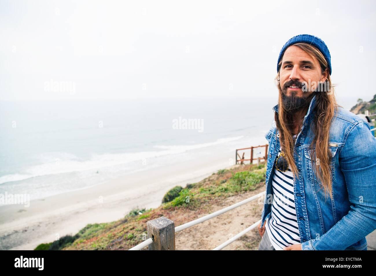 Mid adult man by sea looking at camera - Stock Image