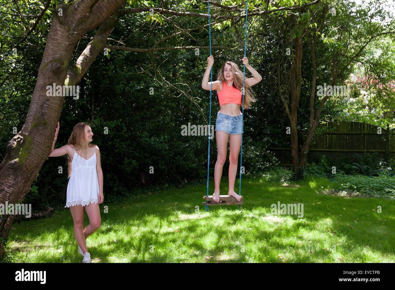 Teenage girl swinging on tree swing, while friend watches on - Stock Image