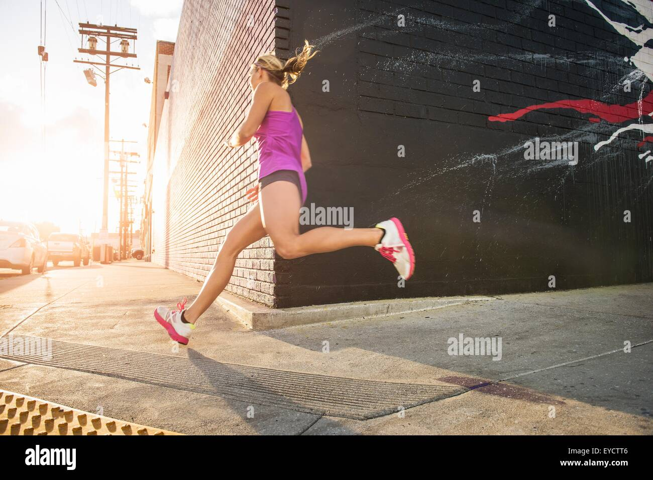 Female runner running along sidewalk - Stock Image