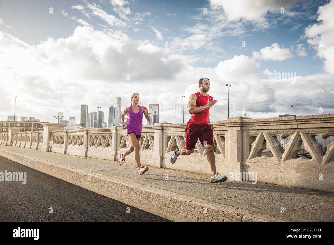 Male and female runners running across bridge, Los Angeles, California, USA - Stock Image