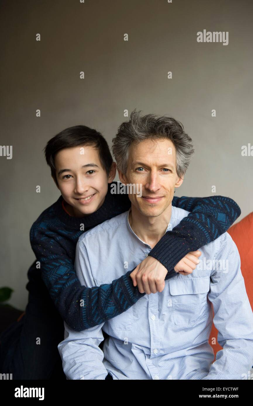 Portrait of teenage boy with arms around father on sofa - Stock Image