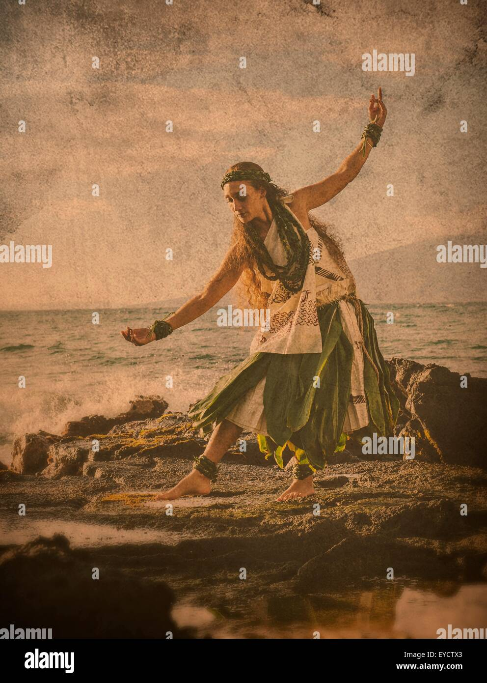Enhanced image of woman hula dancing on coastal rocks wearing traditional costume, Maui, Hawaii, USA - Stock Image