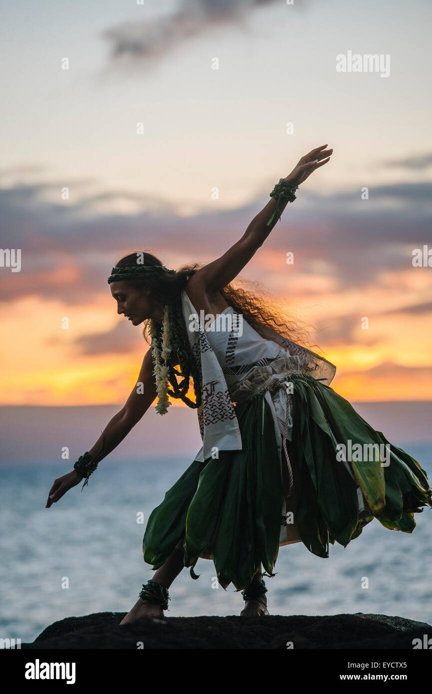Woman hula dancing on coastal rocks wearing traditional costume at sunset, Maui, Hawaii, USA - Stock Image