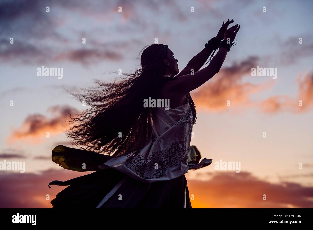 Silhouetted woman hula dancing wearing traditional costume at dusk, Maui, Hawaii, USA - Stock Image