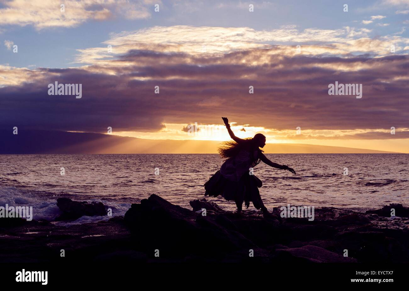 Silhouetted woman hula dancing on coastal rocks wearing traditional costume at sunset, Maui, Hawaii, USA - Stock Image
