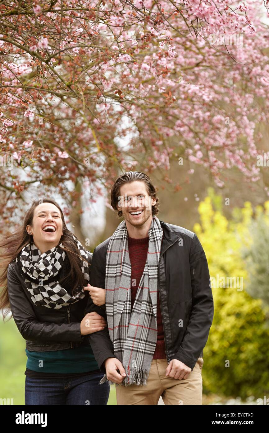 Young couple strolling and laughing in park - Stock Image