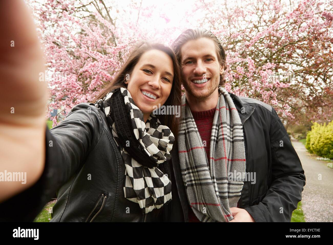 Young couple posing for selfie with blossom in park - Stock Image