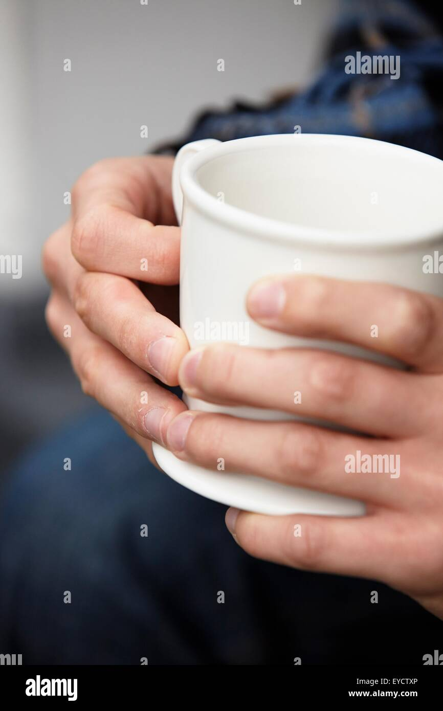 Close up of young mans hands holding coffee mug - Stock Image