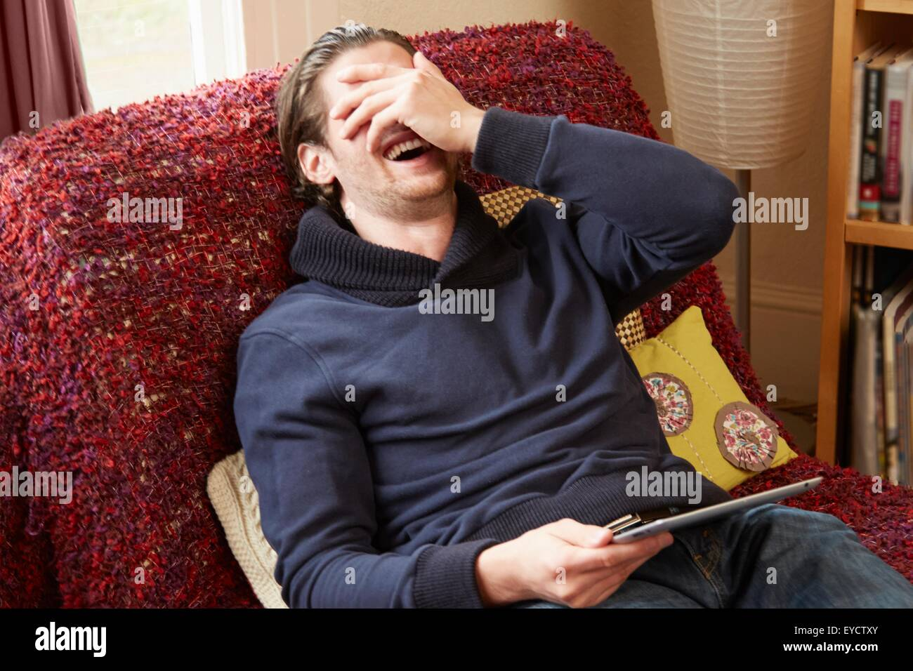 Young man reclining on sofa covering his face whilst laughing - Stock Image