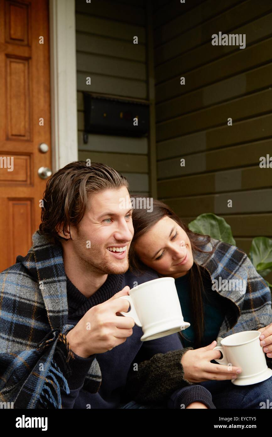 Young couple sitting on porch step wrapped in blanket - Stock Image