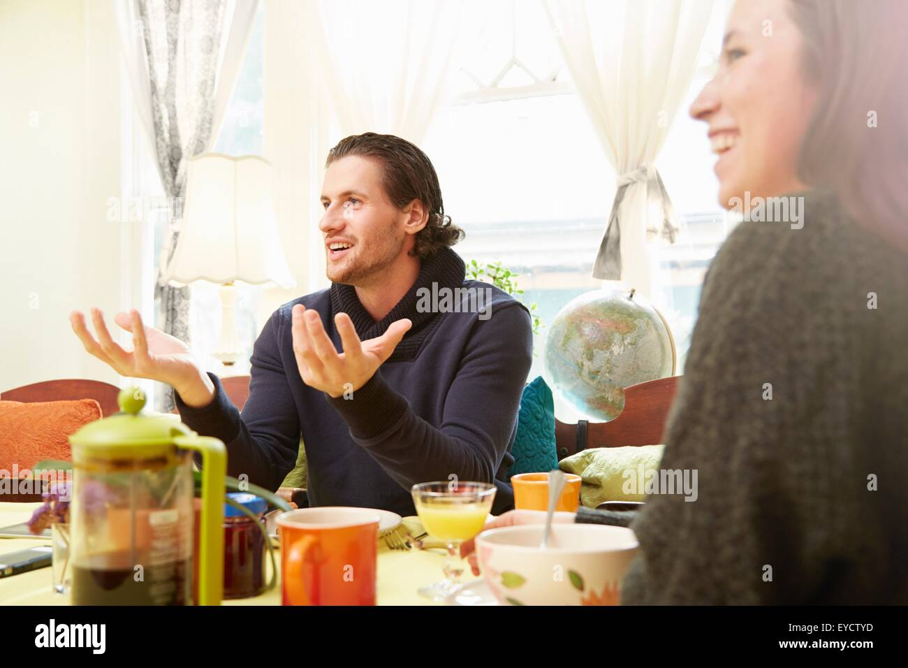 Over shoulder view of young man explaining at breakfast table - Stock Image