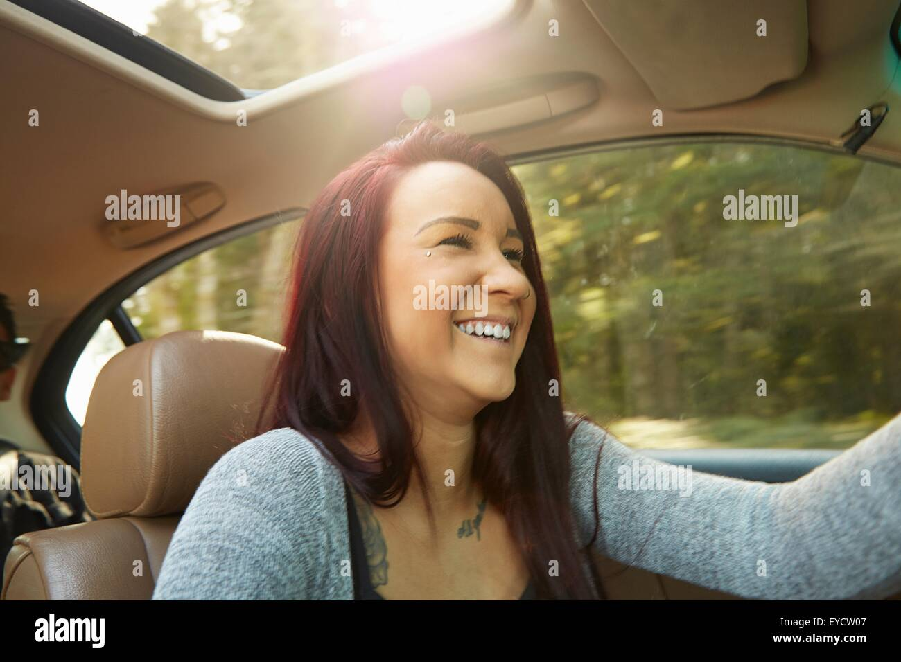 Smiling young woman driving car - Stock Image