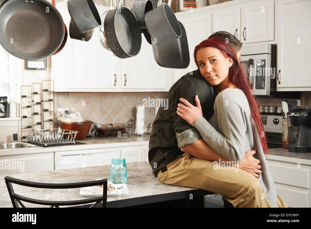 Young couple with heads on each others shoulders at kitchen counter - Stock Image