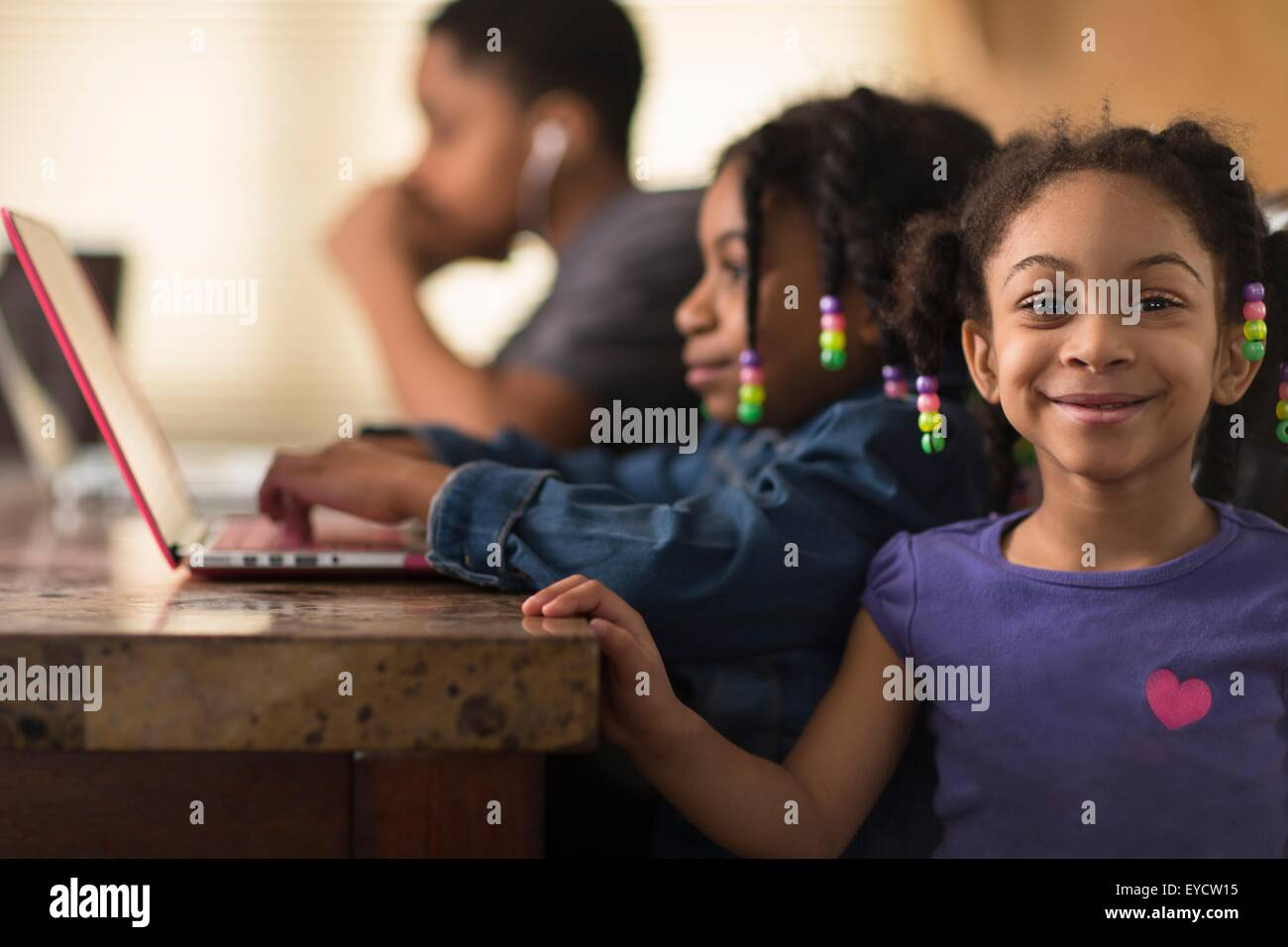 Portrait of girl at dining table and siblings using laptops - Stock Image