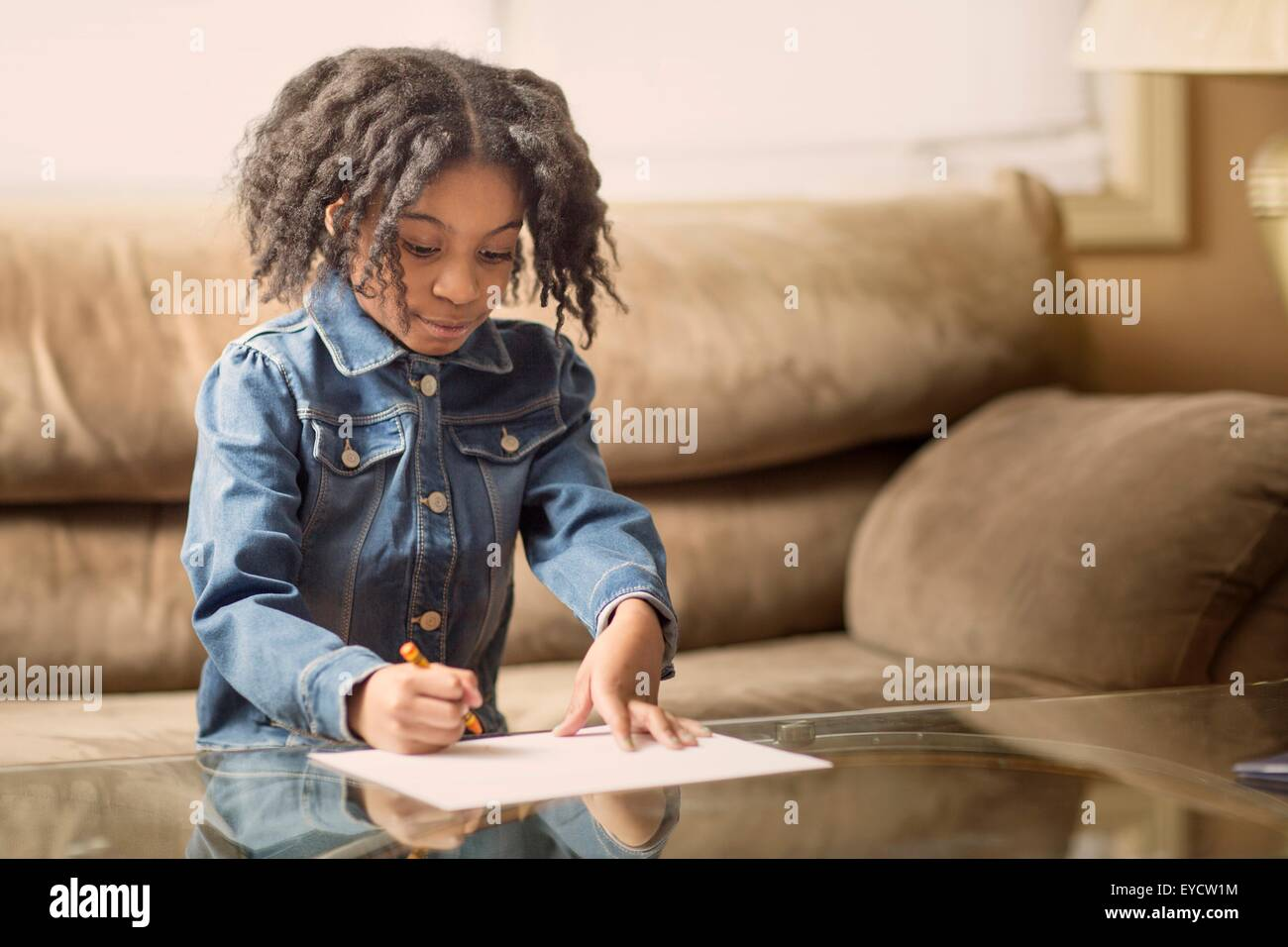 Girl drawing on coffee table - Stock Image