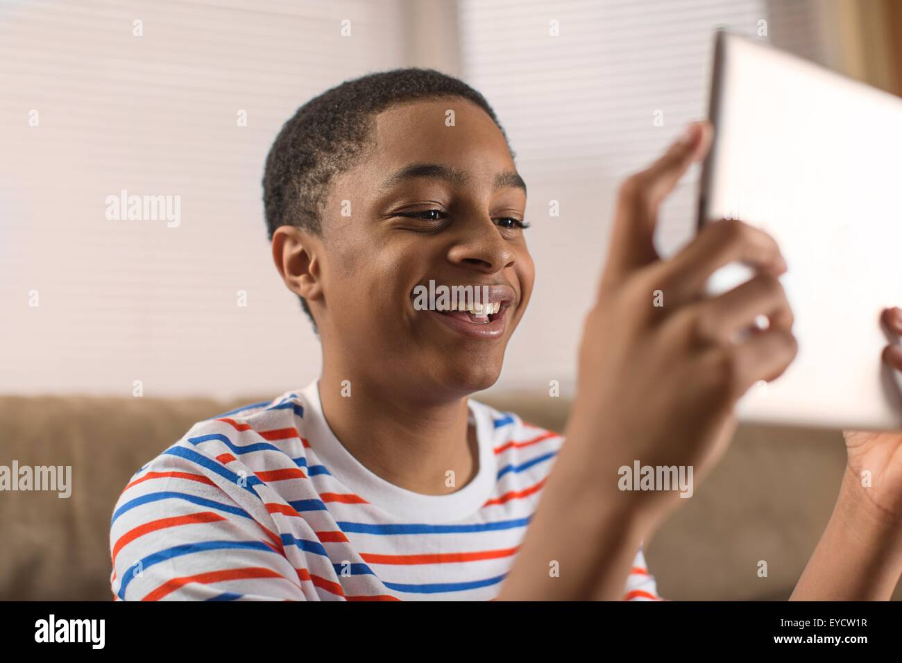 Teenage boy posing for digital tablet selfie on sofa - Stock Image