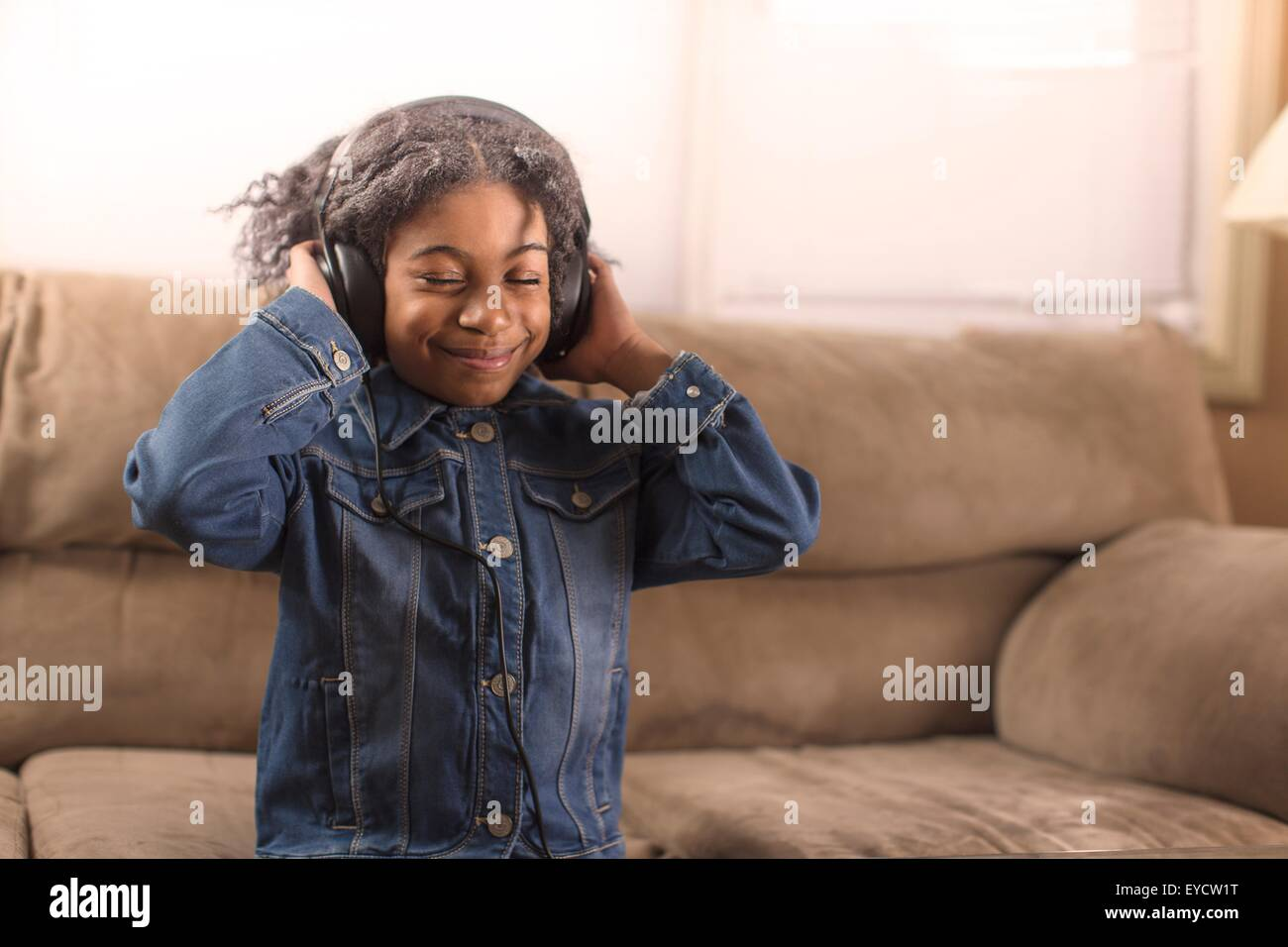 Girl with eyes closed listening to headphone music on sofa Stock Photo