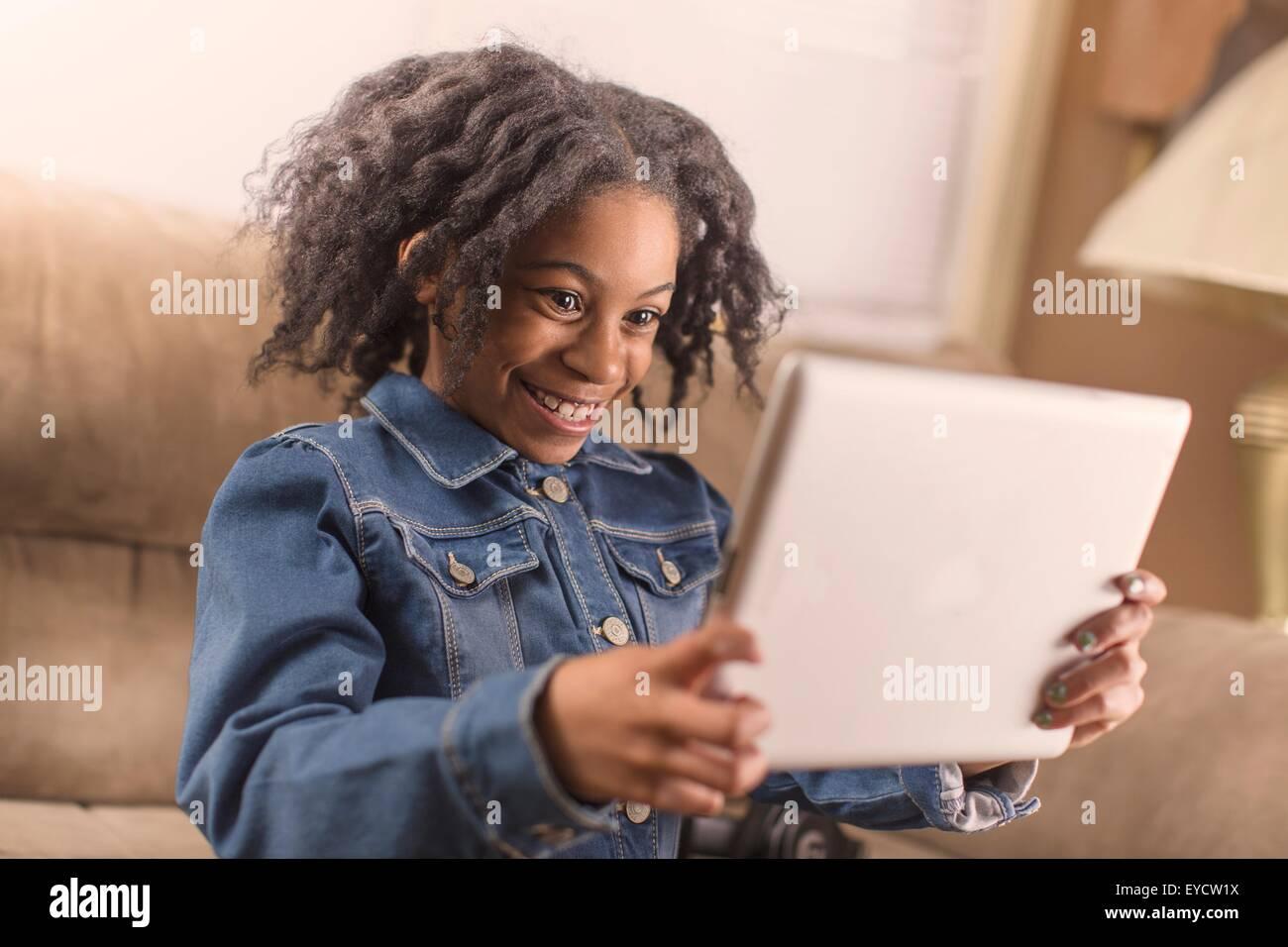 Cute girl posing for digital tablet selfie on sofa Stock Photo
