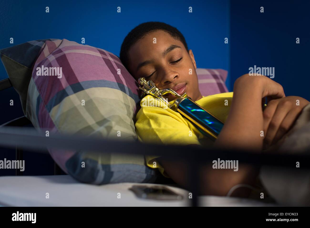 Teenage boy asleep in bunkbed hugging trophy - Stock Image