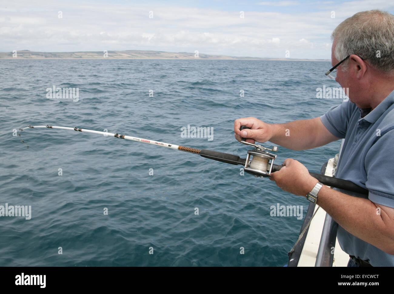 retired gentleman deep sea fishing - Stock Image