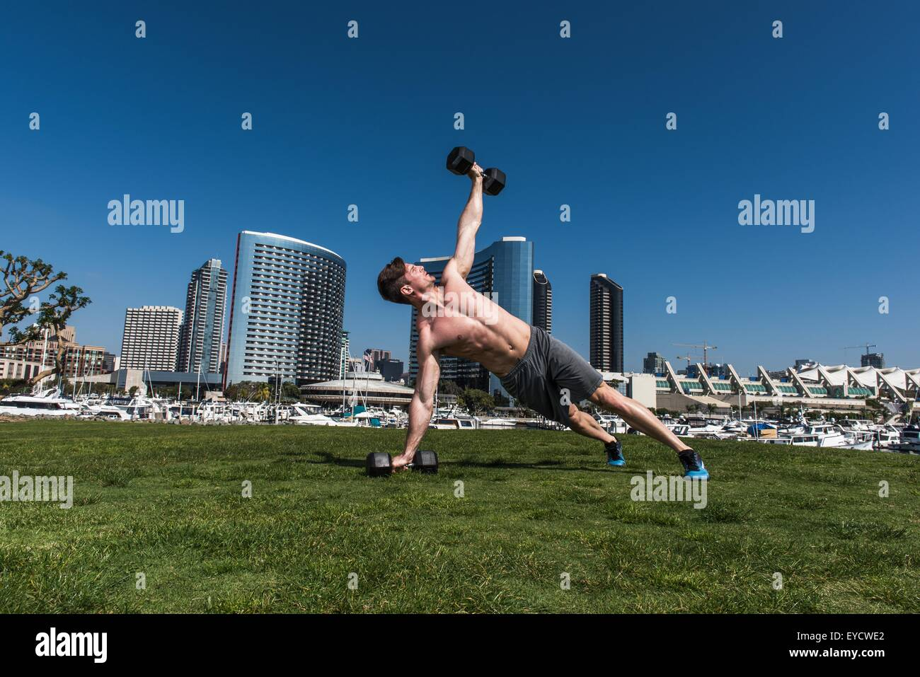 Mid adult man doing one arm push up and lifting dumb bells - Stock Image
