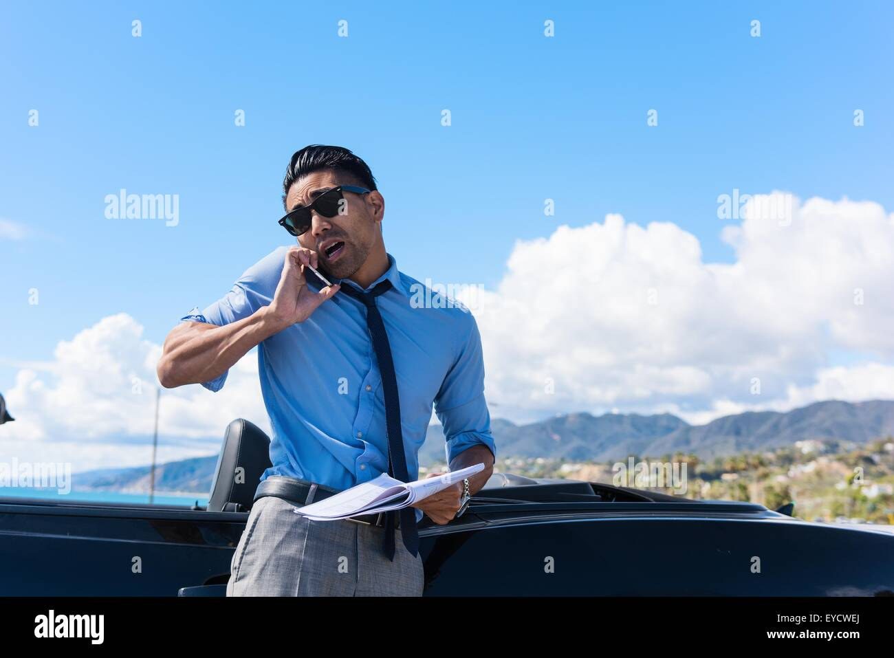 Anxious young businessman at coast parking lot talking on smartphone - Stock Image