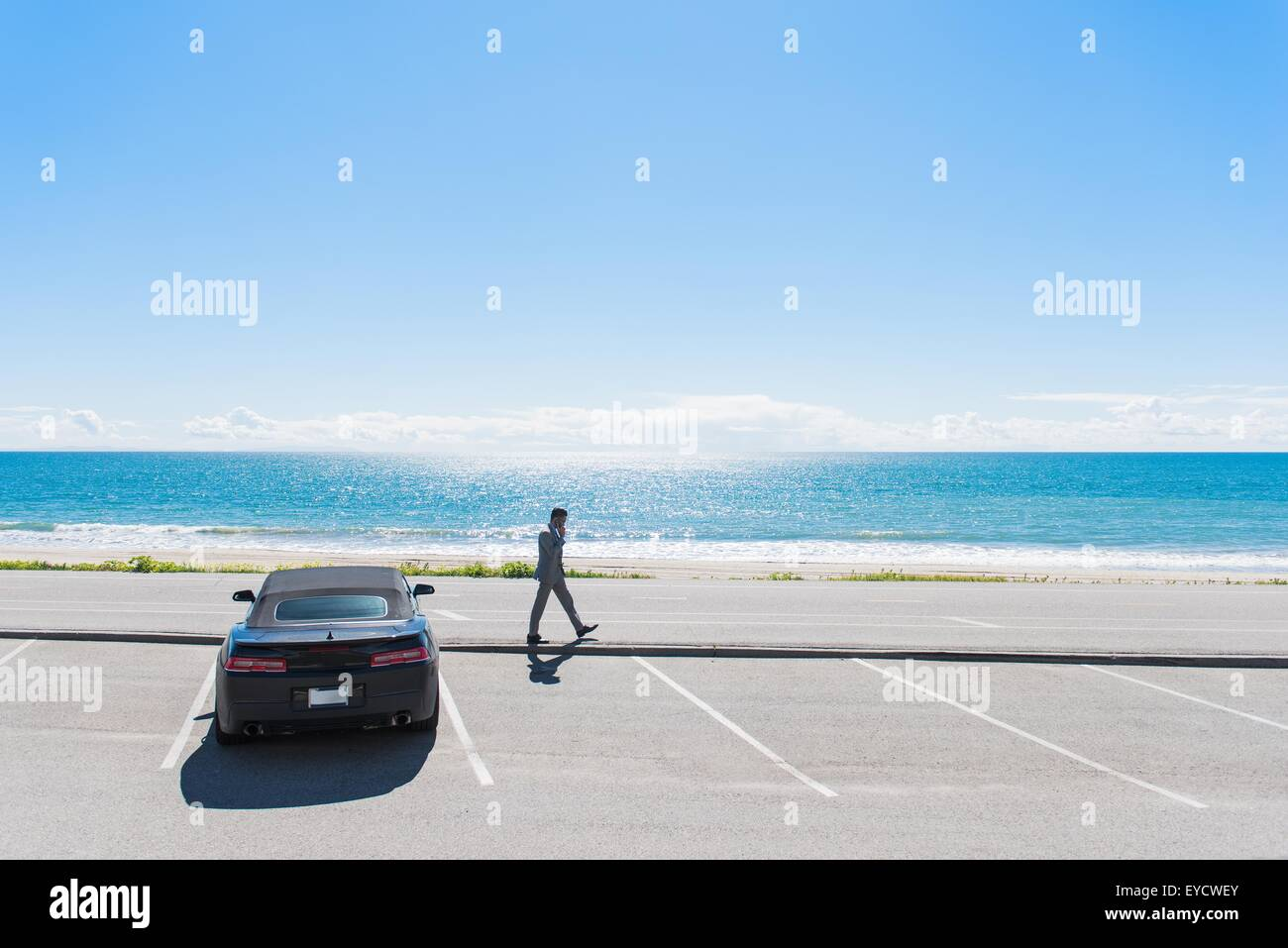Young businessman at coastal parking lot walking whilst talking on smartphone - Stock Image